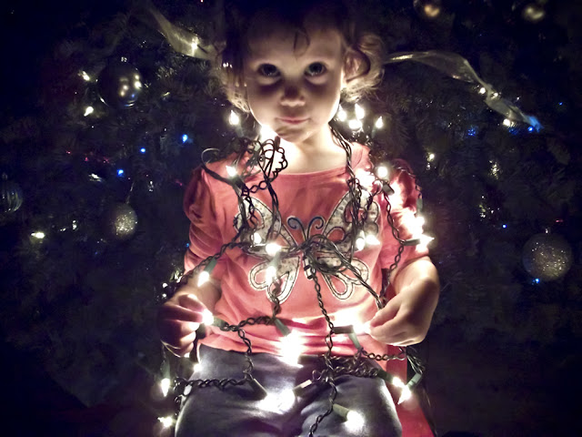 Afton looking at the camera with Christmas lights