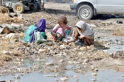 Poor Pakistani Children eating fom Rubble and Trash