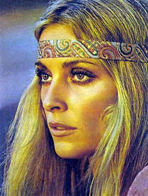 Flower child Sharon Tate sports her heavy Valley of the Dolls-era eye makeup along with a purple caftan and hippie staple, a paisley head band.