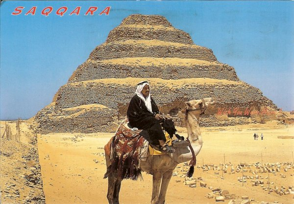 camel and rider in front of a pyramid