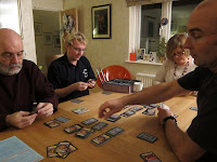 Players deep in concentration during a game of Dominion