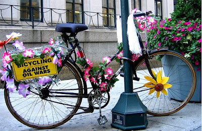 Image of bikes with flowers and Bicycling Against Oil Wars sign