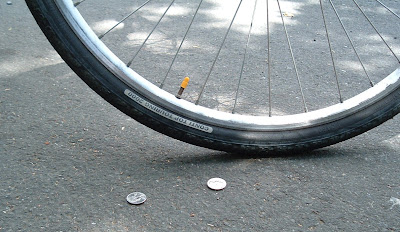 Image of coins near a bicyle tire on the street