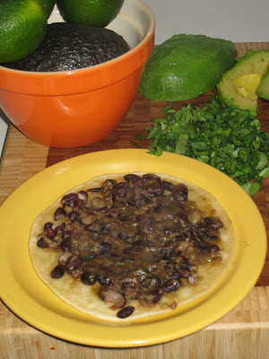 Spread black beans on a crisp corn tortilla