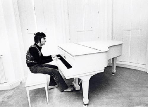 John Lennon at home playing his white piano