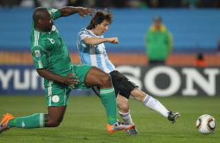 Lionel Messi of Argentina's national football team takes a shot under pressure by Danny shittu of Nigeria during 2010 FIFA World Cup South Africa Group B, Match between Argentina and Nigeria at Ellis Park Stadium on June 12 in Johannesburg, South Africa.