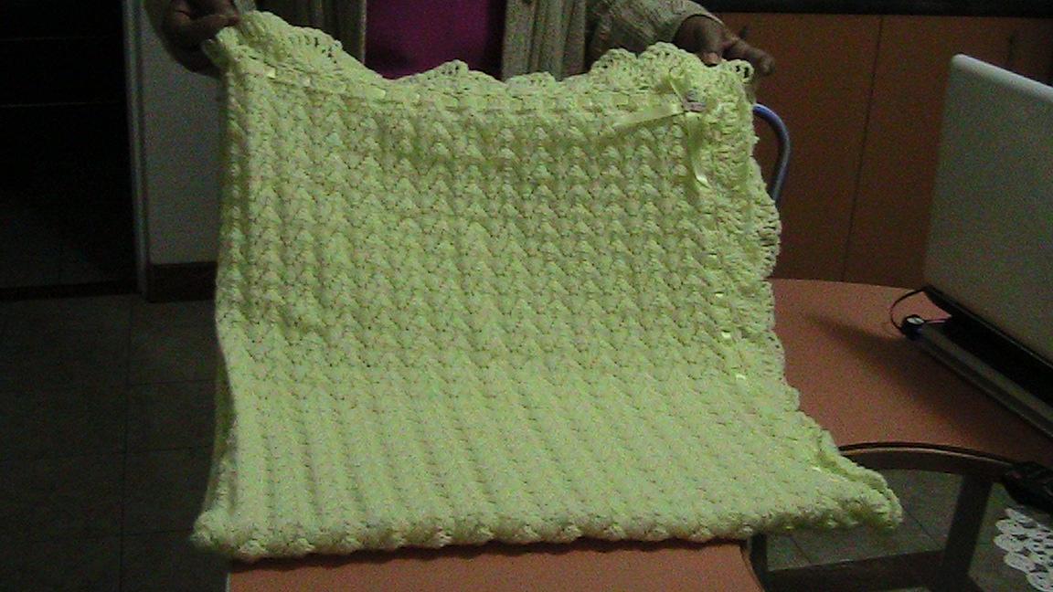 Colcha para bebé tejida a palillo con bordes a crochet