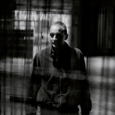 portrait homme derrière des grilles, photo © dominique houcmant
