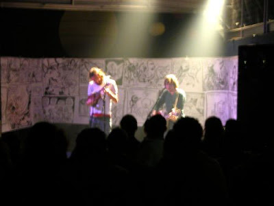 David e Jeff tocam em Poitiers, França. Ao fundo painel de desenhos de Jeff.