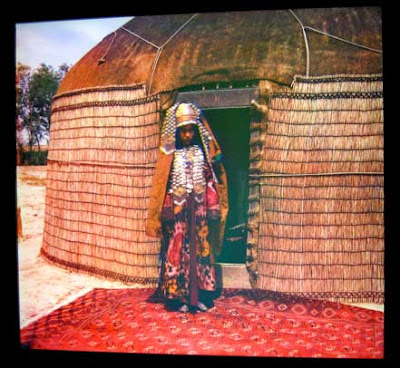 Young woman stands in front of a yurt, a red carpet at her feet