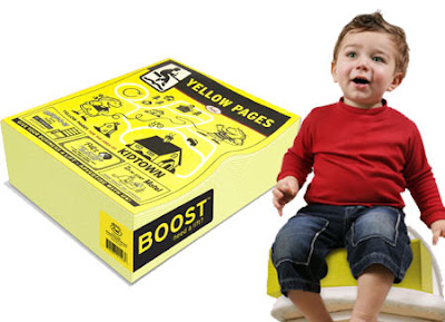 Product photo of a child's booster seat that looks like a big fat yellowpages book