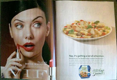 Magazine with two full-page ads. Left ad is a pretty model accidentally putting lipstick onto her right cheek because she's so distracted by what's going on on the other page. But the other page is another ad, this time for a frozen diet dinner.