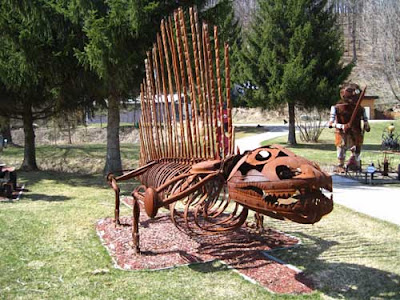 Rusted steel sculpture of a four-legged dinosaur with vertical bars along its spine