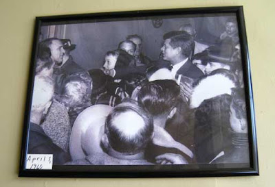 Black and white photo of John F. Kennedy shaking hands in a crowd of people