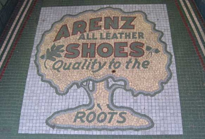 Old tile mosaic of a tree. Words say Arenz all leather shoes, Qualit to the roots