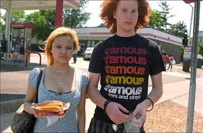 High school age girl and boy at a gas station, color photo