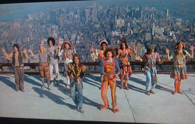 Cast dancing on a rooftop with Manhattan in the background