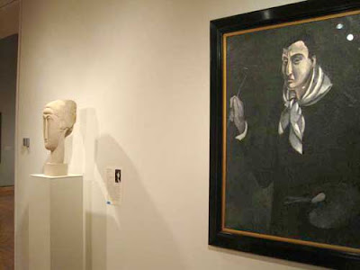 Stylized white marble head sculpture next to a monochrome black and gray painting of a man, head dominant