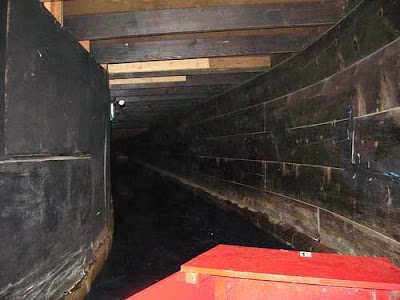 Black-painted curving walls and the fore of a red boat
