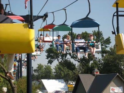 People sitting in multi-colored ski-lift chairs as they ride over the Fair