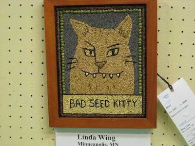Tan cartoon cat with sharp fangs, labeled Bad Seed Kitty