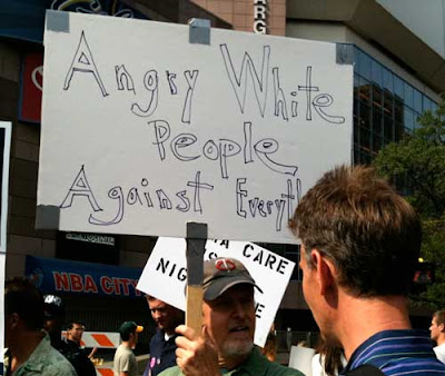Man with sign reading Angry White People Against Everything