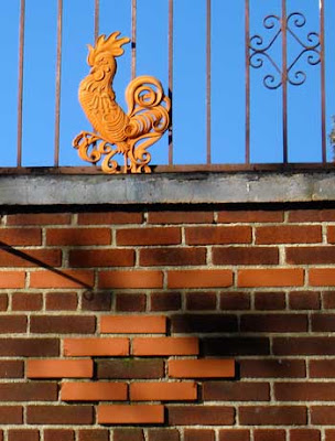 Terra cotta colored metal rooster, part of a fence above decorative brick