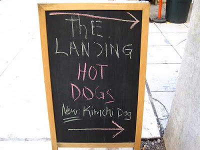 Sidewalk chalkboard sign reading The Landing Hot Dogs then New Kimchi Dogs