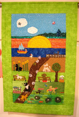 Large wall hanging in green and other bright colors with dogs in a naturalistic setting