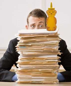 Surprised looking man with a huge pile of file folders in front of him. Atop the pile is a plastic bear bottle full of honey.