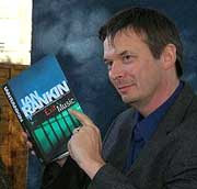 Photo of novelist Ian Rankin with a copy of his book Exit Music
