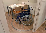 Imaben de una silla de ruedas dentro de un circulo. Sai se puede ver si la habitación esta adaptada y se puede maniobrar