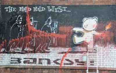 Banksy - Mild Mild West mural splashed with red paint (2009)