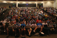An auditorium full of students and every student has a laptop.