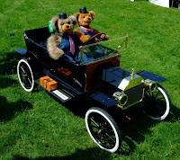 Two bears driving their Model T around the show