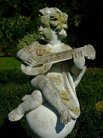 A stone cherub strums silently in the sunshine
