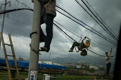 Men repairing power lines by hanging off of them using a sling