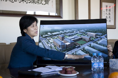 Woman pointing to a large picture of proposed buildings