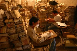 piles of documents, workers in masks