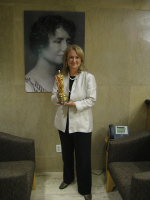 Robin Seaman holding an Oscar statuette in front of a picture of Helen Keller