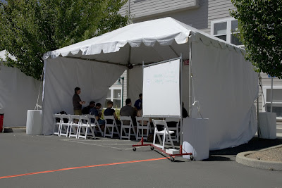 Tent with chairs and people in a meeting session