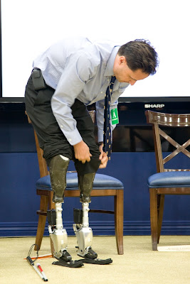 Hugh Herr bending over to lift his pant legs and show off his biohybrid feet