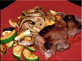 cowboy steak with sauteed onions and zucchini