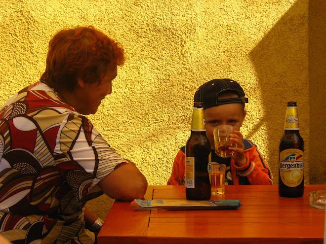 Un copil se răcoreşte cu o bere rece,sub privirea atentă a bunicii