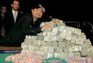 World Series of Poker Main Event Champion Jerry Yang poses with his prize money and his new favorite hand - pocket 8s