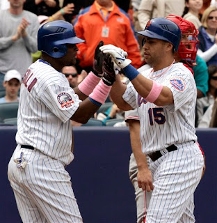 Carlos Beltran and Luis Castillo hold hands while wearing pink wristbands