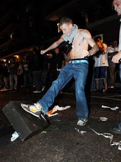 a shirtless Penn State fan stomps on a downed light pole