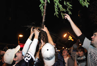 Penn State fans worship a tree they tore out of the ground during celebrations after beating Ohio State
