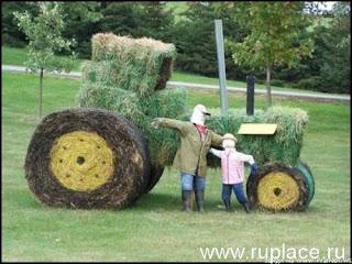 Креативный трактор. Два чучела возле трактора из сена.
