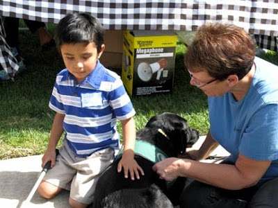 A youngster meets a black Lab Guide Dog puppy at the Blind Babies Foundation beep Easter egg hunt